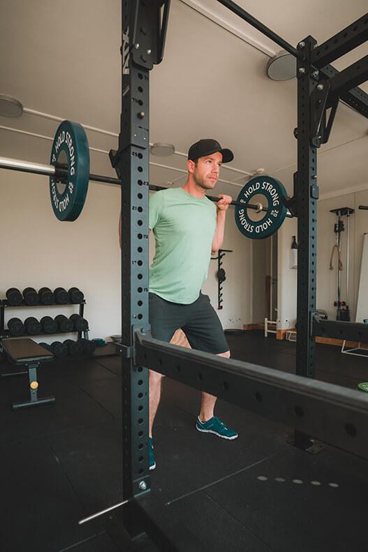 Kraftraum Training mit der Langhantel Back Squats und Kniebeuge mit Gewichten